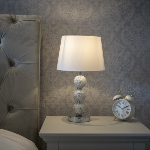 beautiful silver lamp and old fashioned alarm clock sitting on bedside table in front of wall with silver damask pattern wallpaper