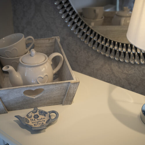 dressing table with teapot and cups, silver lamp and large mirror