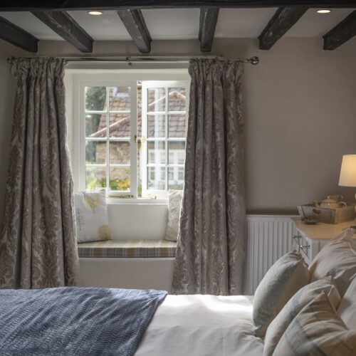 beautifully furnished bedroom with window overlooking sleepy country village