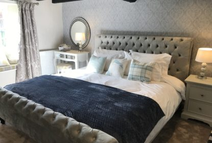 richly furnished bedroom with beamed ceilings and large queen sized bed