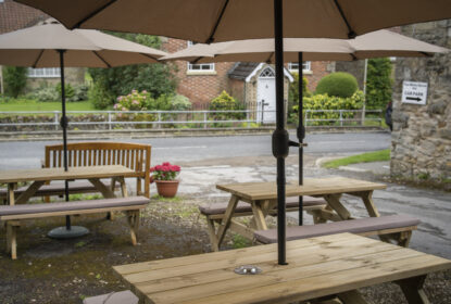 picnic tables with parasols in beer garden next to sleepy country road