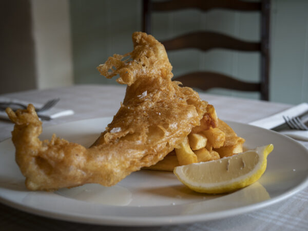 super crispy battered fish and chips on a plate with slice of lemon
