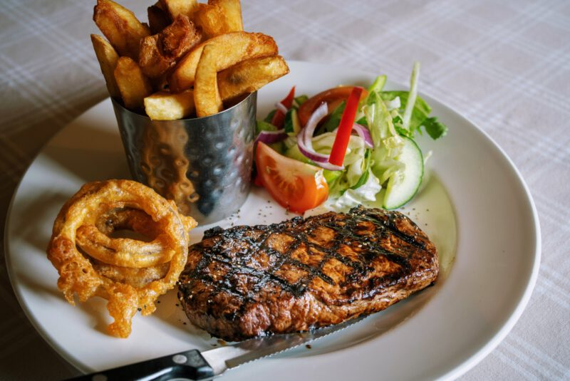 grill seared steak on a plate with a bowl of crispy chips and served with onion rings and salad
