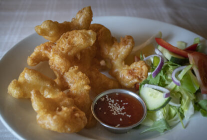 crispy battered shrimp on a plate with sweet chilli dipping sauce and side salad