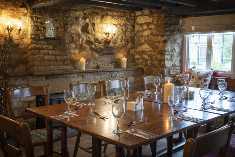 dining table for 10 in a cosy candle lit pub room with wooden beamed ceilings and a log burner
