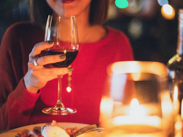 Woman holding a glass of red wine whilst eating at a candlelit table
