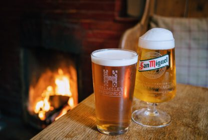 two pints of beer on table bathed in the warm light of a roaring log fire