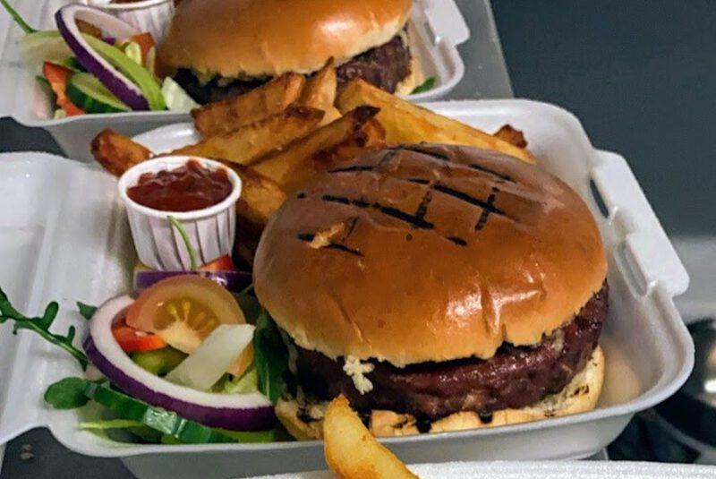 burgers and chunky chips with salad and ketchup pot in a takeaway container
