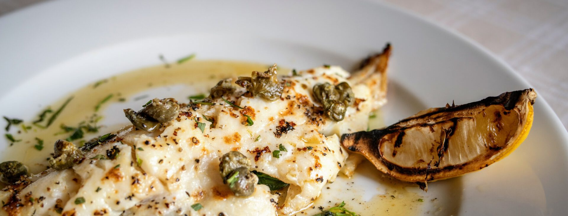 lightly browned piece of white fish on a plate with slice of lemon and drizzled in a buttery sauce