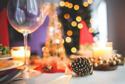 Table top laden with christmas dinner and fetive decorations in the background