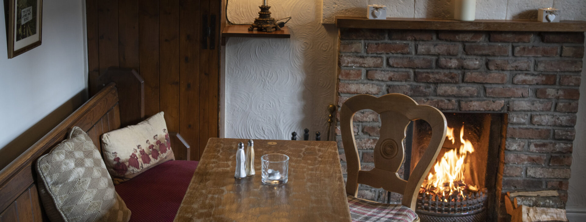 cosy pub table next to roaring log fire